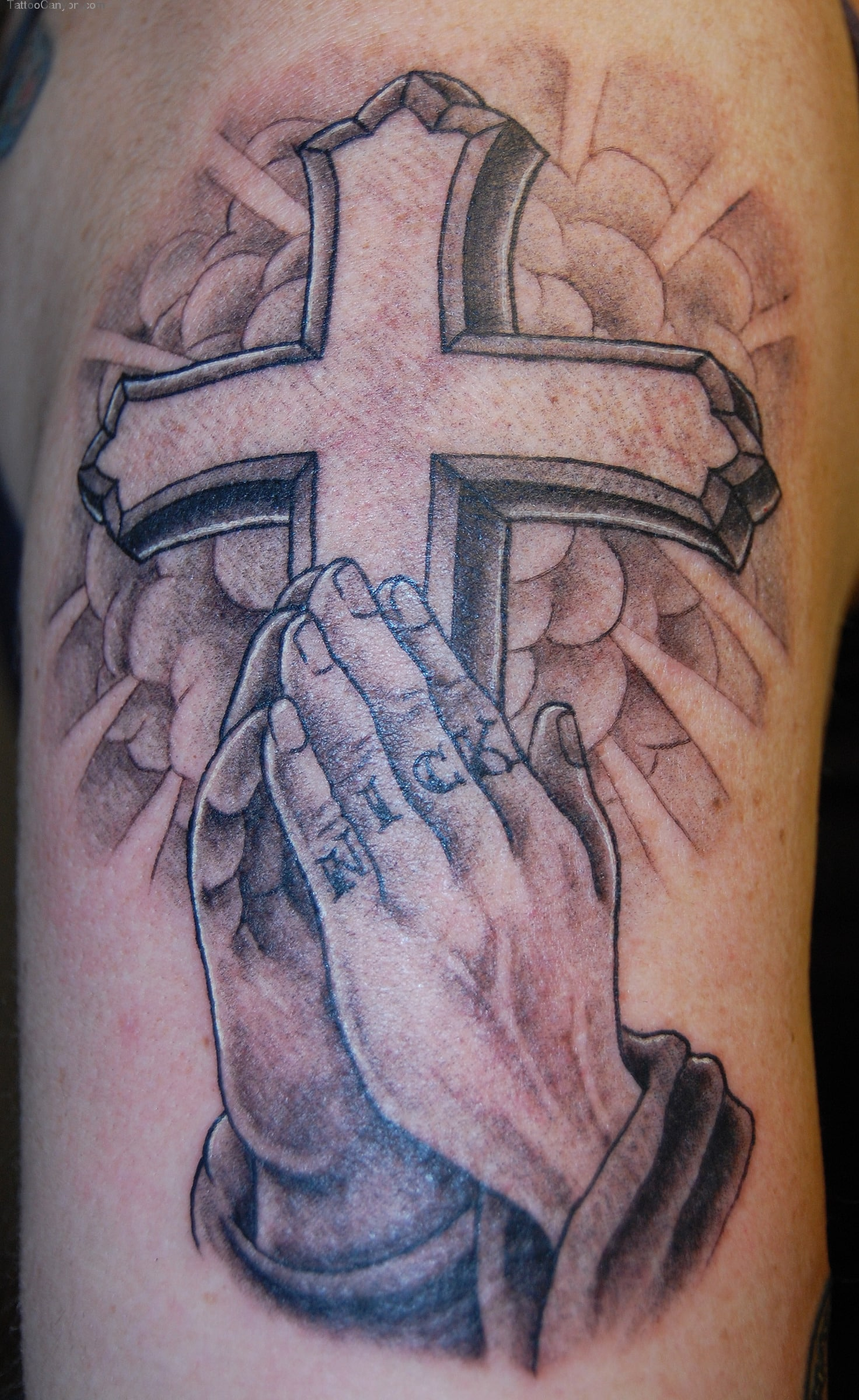 christian cross with praying hands tattoo