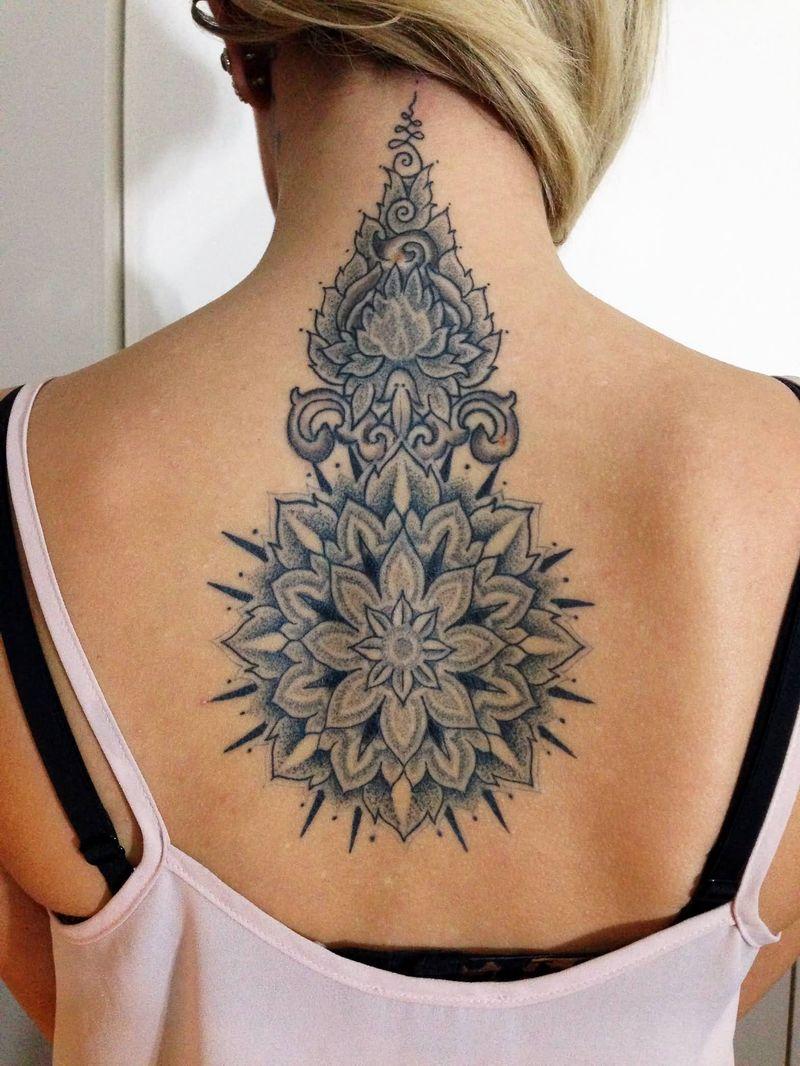 grey ink amazing flower tattoo design on girl spine
